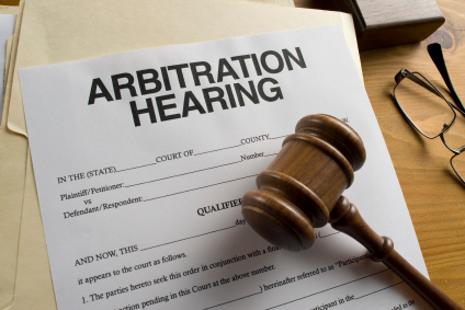 "a gavel over a paper that says ""arbitration hearing"""