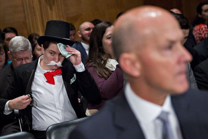 Amanda Werner of Americans for Financial Reform and Public Citizen sits in costume behind Richard Smith, former chairman and chief executive officer of Equifax Inc., right, before a Senate Banking Committee hearing in Washington, D.C., U.S., on Wednesday, Oct. 4, 2017. Lawmakers grilled Smith on Tuesday after hackers attacked the company's systems and got access to sensitive information for 145.5 million Americans. Photographer