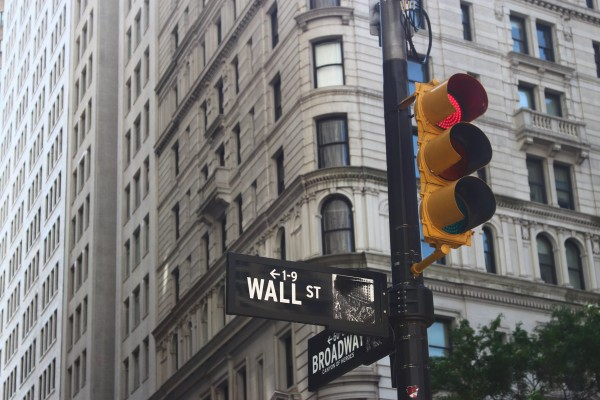 Wall Street sign and a stoplight turned red - Photo by Roberto Júnior on Unsplash
