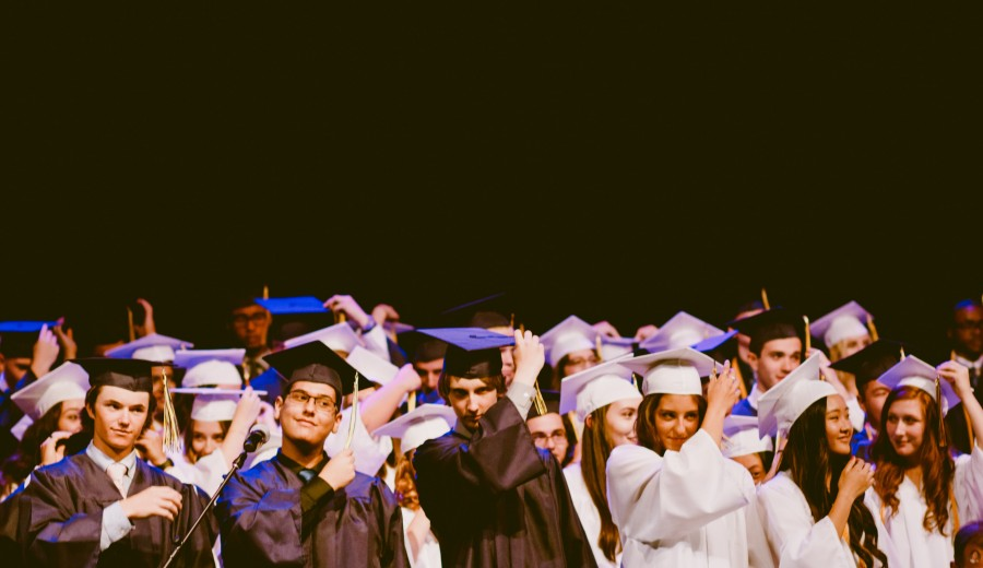 students in graduation cap and gowns - Photo by Caleb Woods on Unsplash