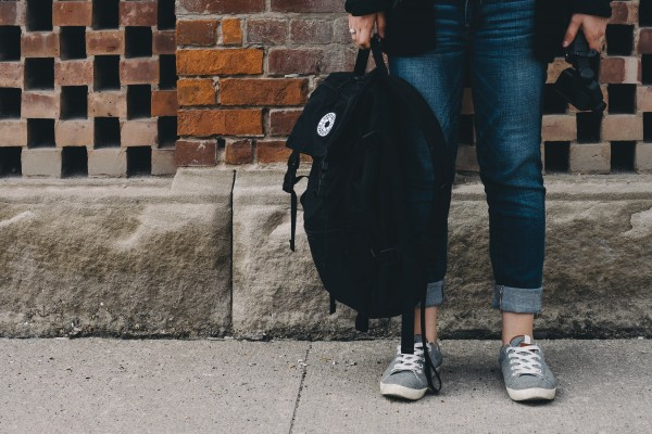 a student holding a black backpack standing in front of a brick wall -Photo by Scott Webb on Unsplash
