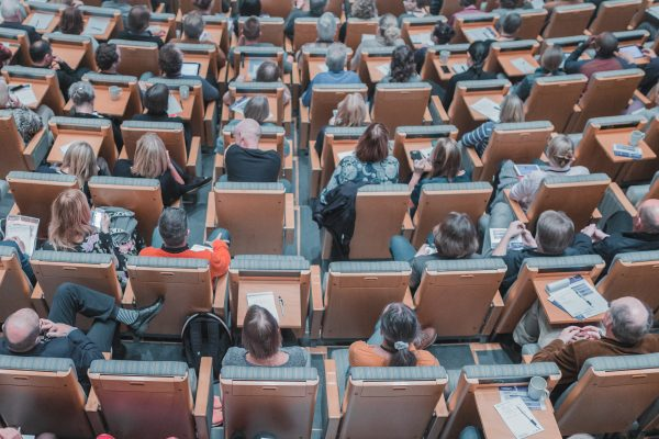 a large group of students in an auditorium sitting in chairs Photo by Mikael Kristenson on Unsplash