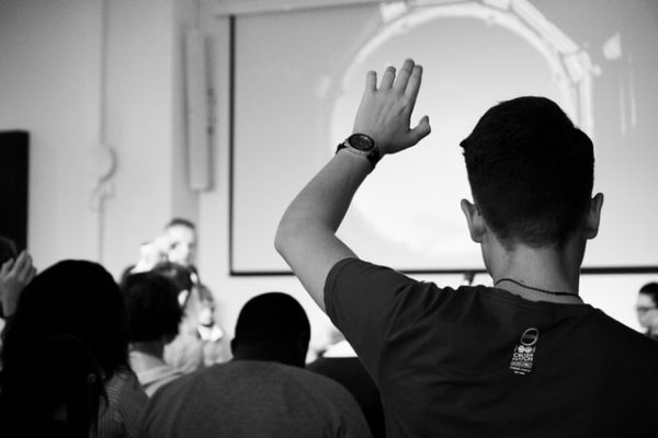 a student raises their hand in a classroom Photo by Felicia Buitenwerf on Unsplash