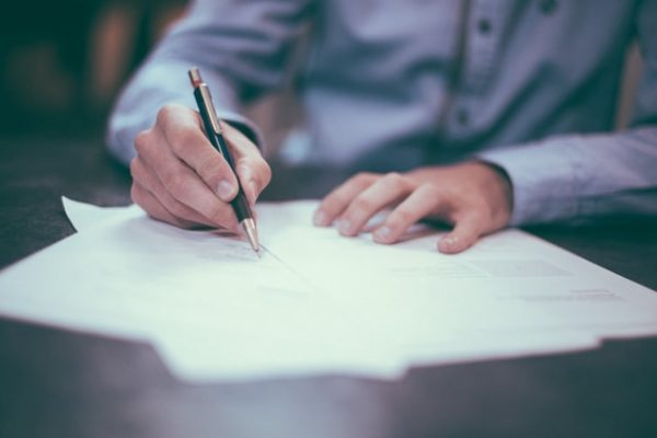 lawyer signing a document Photo by Helloquence on Unsplash