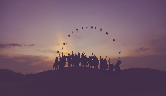 student graduates thowing their caps into the air